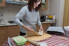 Thuis voorbereidend Pizza: Vrouw die een Heerlijke Pizza in de Keuken maken royalty-vrije stock foto's