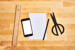 Thuiswerkconcept Smartphone, een leeg blad van document en bureau of schoollevering stock fotografie