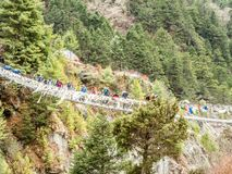 Thukla, Nepal 04/13/2018: Trekkers, welche die Brücke auf Weg zu niedrigem Lager Everest kreuzen Stockfotografie