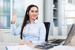 Thum up by spokeswoman at call center. Motivational gesture Royalty Free Stock Photo