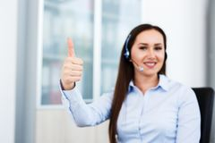 Thum up by spokeswoman at call center. Motivational gesture Stock Photos