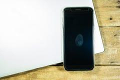 Thumb система безопасности уединения отпечатка пальцев на черном экране мобильного телефона на серебряной компьтер-книжке на дере Стоковые Изображения RF
