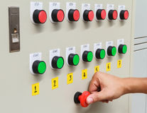 Thumb касание на красном переключателе аварийного стопа и зеленой кнопке старта Стоковые Изображения RF