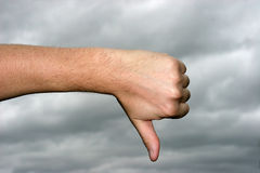 Thumb down. With gray storm sky in the background royalty free stock photo