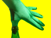 Thumb in a Green Bottle. Hand with gloves puts the thumb in a green bottle, isolated on neon yellow background Stock Photography