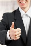 Thumb of a hand lifted upwards as success gesture Stock Image