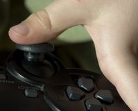 Thumb on a joypad. A child´s thumb on a gamepad or joypad Stock Image