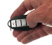Thumb on keyless wireless door opener. Black modern car door opener and keyless entry device with thumb pressing lock Stock Images
