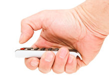 Thumb man's hand presses the red button. The remote control in a man's hand. On a white background Royalty Free Stock Image