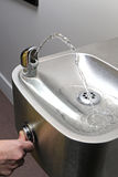 Thumb press the drinking water fountain Stock Images