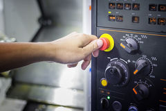 A Thumb ready to press emergency Stop button on Control panel of Royalty Free Stock Photography