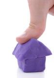 Thumb squash house. Thumb crushing house symbol of crashing housing market Royalty Free Stock Photography