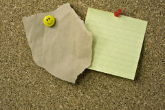 Thumb tacks and notes on corkboard Royalty Free Stock Photos