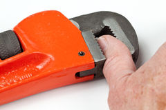 Thumb trapped in red wrench Stock Image