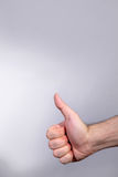 Thumb up. Hand on gray background; space for copy stock images