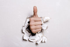 Thumb Up. The fist has punched to itself hole in wall and shows that all is excellent Stock Photography