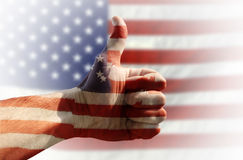 Thumb up. Hand with thumb up and american flag in background Stock Photography
