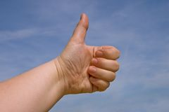 Thumb up. Fist with a thumb up against blue sky Stock Image