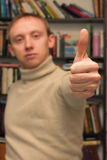 Thumb up on background of man and bookshelves. Human hand with thumb up on background of proud man and bookshelves Royalty Free Stock Image
