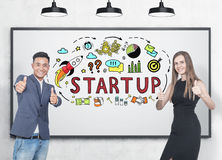 Thumb up business partners, startup. Asian businessman and his blonde colleague wearing an elegant black dress. They are showing thumb up signs and smiling Royalty Free Stock Images