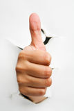 Thumb up from crack wall Stock Image