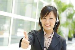 Thumb up Customer Representative. Friendly Customer Representative with headset thumb up during a telephone conversation Royalty Free Stock Photos