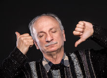 Thumb up and down. Thoughtful elderly man with closed eyes and thumb up and down Stock Photo