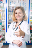 Thumb up druggist. Young smiling druggist in pharmacy store with thumb up Royalty Free Stock Image