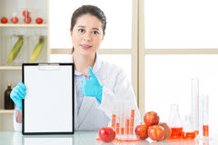 Thumb up for good genetic modification food test. Record on clipboard royalty free stock images