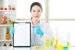Thumb up for good genetic modification food test record. On clipboard stock photo