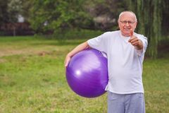 Thumb up for healthy exercising - Happy senior man with fitness royalty free stock photo