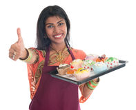 Thumb up Indian woman baking cupcakes. Happy Traditional Indian woman in sari baking bread and cupcakes and showing thumb up, wearing apron holding tray isolated Royalty Free Stock Photos