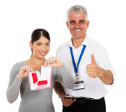 Thumb up learner driver. Happy driving instructor giving thumb up and learner driver tearing L sign Stock Photos