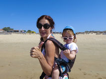 Thumb up mother and baby in backpack Stock Photo