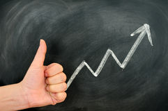 Thumb up with a positive growth arrow stock photo