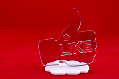 Thumb up shape on a white cloud. Silver thumb up shape made of plexiglas standing on a cloud shape on a red background stock image