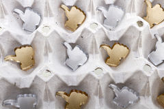 Thumb up shapes background. Golden and silver thumb up shapes made of plexiglas lie inside of a paper egg tray Stock Images