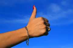 Thumb Up Sign. Woman's hand showing thumb up sign over blue sky Stock Photography