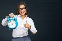 Thumb up. Smiling business woman holding clock. Black background Royalty Free Stock Photo
