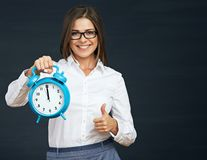 Thumb up. Smiling business woman holding clock. Black background Stock Photos