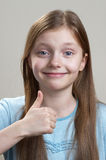 Thumb Up!. Smiling schoolgirl portrait gesturing thumb up over grey background Stock Photos