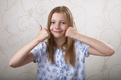 Thumb Up!. Smiling schoolgirl portrait gesturing thumb up over grey background Royalty Free Stock Image