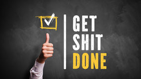 Thumb up to slogan 'Get Shit Done'. Written on a chalkboard royalty free stock photography
