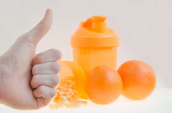Thumb up to the sport nutrition with white background. Thumbs up  with orange , shaker, vitamins on white background. Prepare for summer Stock Images