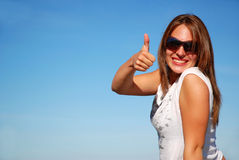 Thumb up woman. Attractive young woman model with long red hair, wearing sunglasses, holding her thumb up to show her excitement about her happy holidays in Stock Photos