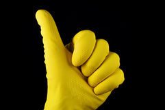 Thumb up in yellow rubber glove. On black background Royalty Free Stock Photo