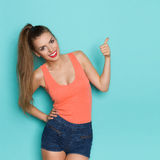 Thumb Up For This. Young attractive woman in jeans shorts and orange shirt showing with thumb up. Three quarter length studio shot on teal background Royalty Free Stock Photo