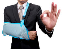 Thumb up young businessman with broken hand wearing Stock Images
