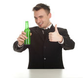 Thumb up young man with bottle of beer. Standing happy young man in black suit with bottle of beer, thumb up Stock Photos