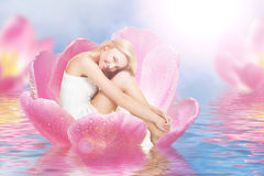 Thumbelina on tulip. Young cute woman as thumbelina sitting in tulip stock images